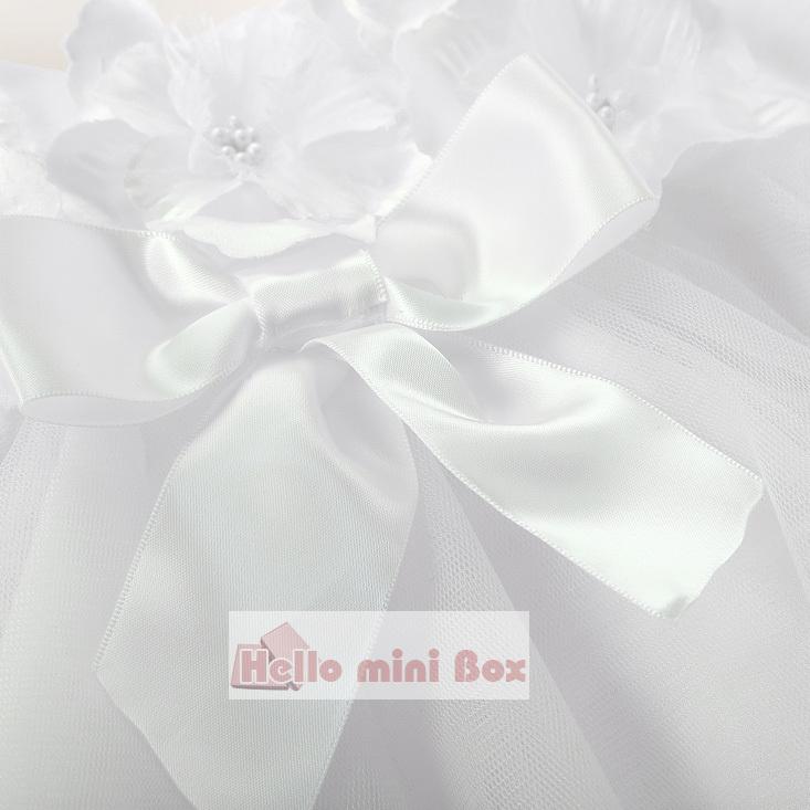 Un vestido de bautizo corto y suave con flores y lazos en el pecho.