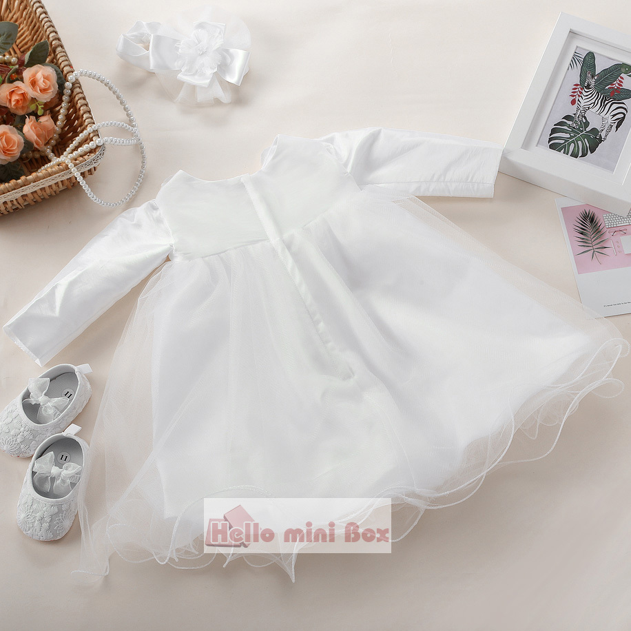 A short soft net christening dress with flowers and bows on the chest