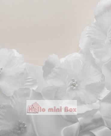 Een korte zachte net doopjurk met bloemen en strikken op de borst