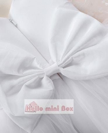Delicado vestido de bautizo de doble encaje con un gran lazo en la espalda.